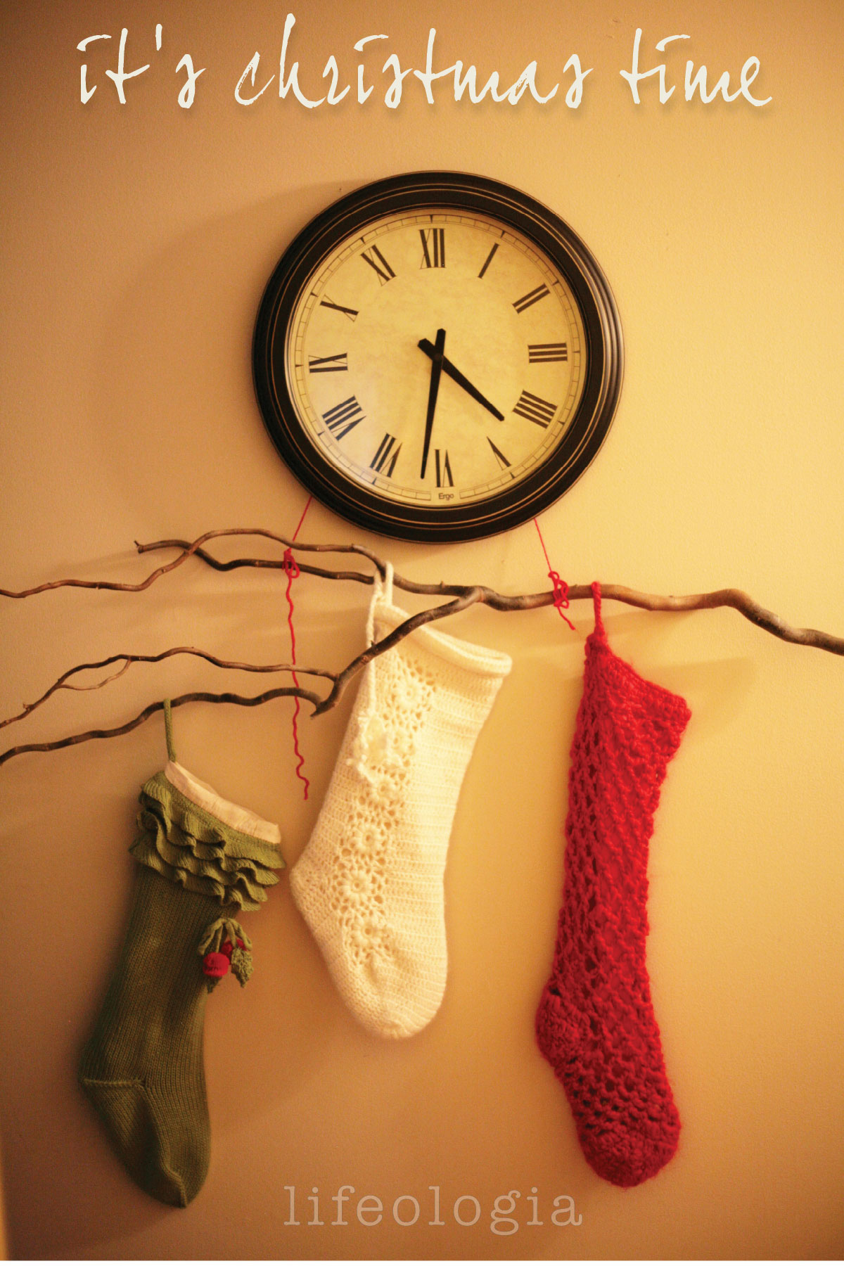 christmas-decorating branch with stockings hung from a clock